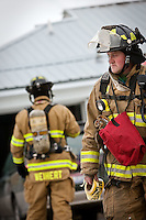 JEROME A. POLLOS/Press..Coeur d'Alene firefighter Jake Bieker looks for an area to secure caution tape while crews extinguish an attic fire caused by electrical wiring at a home Tuesday on 11th Street in Coeur d'Alene. The fire is believed to be caused by snow sliding off the roof which severed electrical lines near the eaves. Homeowners are reminded to not only protect electrical and gas lines that enter the home from snow falling from rooftops, but to also have a working smoke detector and clear snow from hydrants near their home.