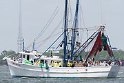 A decorated shrimp boat parades down the Cooper River during the annual Blessing of the Fleet signifying the start of the commercial shrimping season April 30, 2017 in Charleston, South Carolina. Coastal shrimping is part of the low country heritage but has been declining rapidly with rising costs and increased foreign competition.