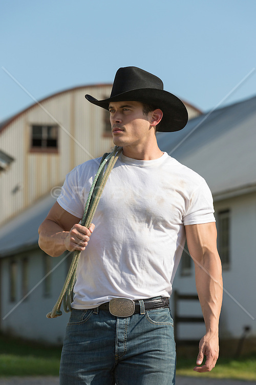 rugged cowboy wearing a white tee shirt on a ranch