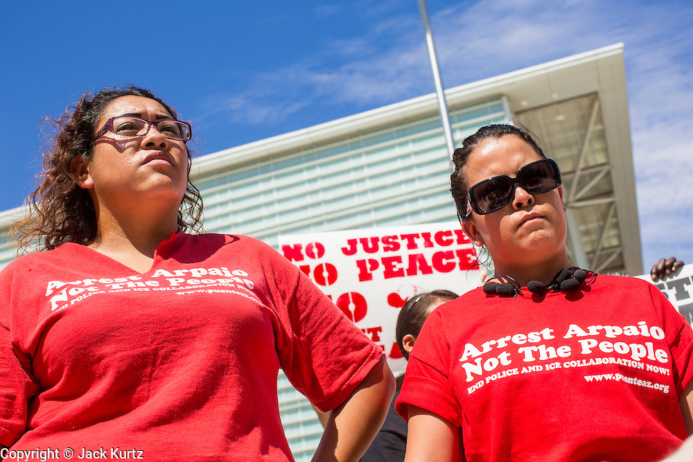 "19 JULY 2012 - PHOENIX, AZ: LETICIA RAMIREZ (left) and NATALLY CRUZ (right) both from Puente, a human rights organization, speak out against Maricopa County Sheriff Joe Arpaio in front of the US Courthouse on the first day of a class action lawsuit, Melendres v. Arpaio in Phoenix Thursday. The suit, brought by the ACLU and MALDEF in federal court against Maricopa County Sheriff Joe Arpaio, alleges a wide spread pattern of racial profiling during Arpaio's ""crime suppression sweeps"" that targeted undocumented immigrants. U.S. District Judge Murray Snow granted the case class action status opening it up to all Latinos stopped by Maricopa County Sheriff's Office deputies during the crime sweeps. The case is being heard in Judge Snow's court.   PHOTO BY JACK KURTZ"