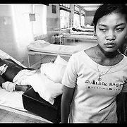 "Corn Poy, wife of Nil Sarak, and Heng Sath, mother, leave Saturday, March 20, 1999, after visiting  Sarak at the the modern trauma facility ""Emergency"" in Battambang, Cambodia.  Sarak had his right leg amputated after he was injured by a landmine while attempting to clear land for the family in Bavil provience."