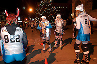 Granite State Roller Derby Elves skate around City Plaza Friday evening as folks stroll the streets during the Midnight Merriment festivities.  (Karen Bobotas/for the Concord Monitor)