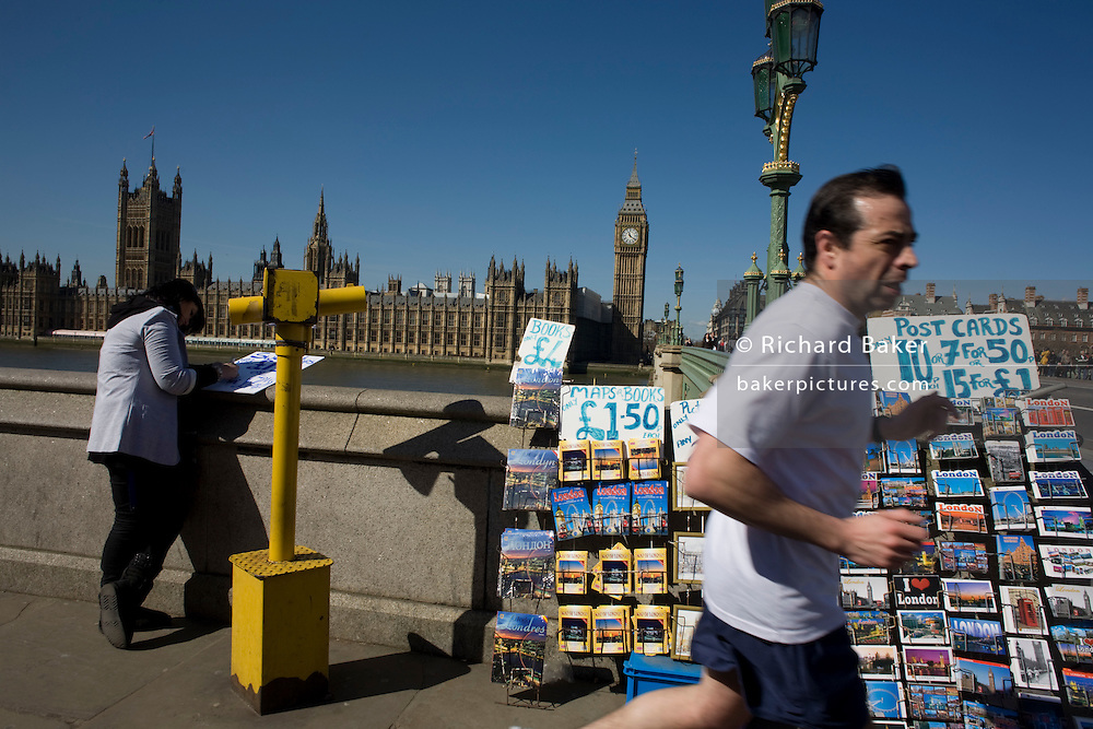 The tower containing Big Ben amid the Gothic architecture of Britain's Houses of Parliament and jogger on the Embankment. Passing-by at speed with a slight blur, the male sportsman runs by the racks of colourful postcards showing London scenes, their prices written on makeshift marker on a white board. Beyond is Westminster Bridge that stretches of the River Thames, towards the British Houses of Parliament, with Big Ben's clock tower rising high above. It is a fine sunny day and a woman is writing more prices for tourist mementoes of another board, leaning on the river wall. The House of Commons is the lower house of the Parliament of the United Kingdom, which also comprises the Sovereign and the House of Lords (the upper house). Both Commons and Lords meet in the Palace of Westminster.