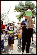 Kids and adults march in Earth Day parade in rain-forest theme costumes; Forest Park, St Louis. Missouri