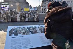 """© Licensed to London News Pictures. 06/02/2018. LONDON, UK.  A visitor views a pop-up exhibition featuring 59 life-sized images of campaigners, along with famous rallying slogans such as """"deeds not words"""" in Trafalgar Square marking 100 years since the Representation of the People Act was passed, granting some women over the 30 in the UK the right to vote for the first time.  Photo credit: Stephen Chung/LNP"""