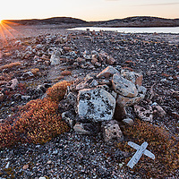 Canada, Nunavut, Territory, Setting sun lights stone cairn and wooden cross on Harbour Islands along Hudson Bay near Arctic Circle