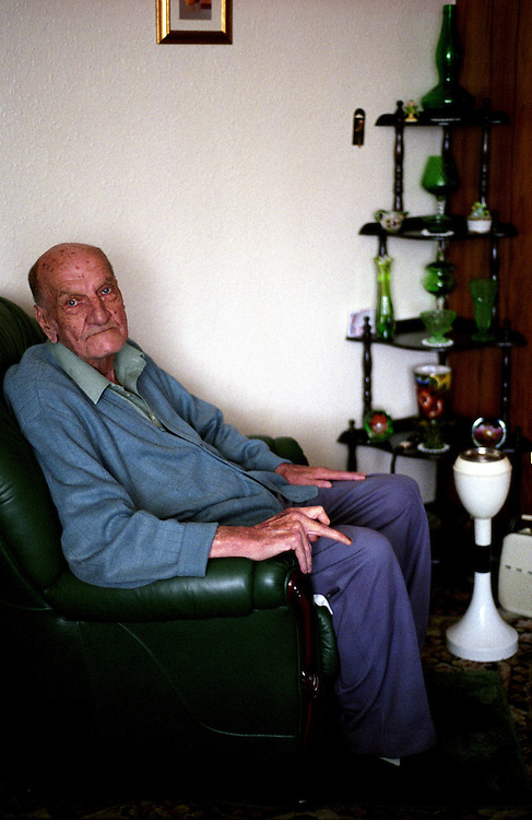 One of the North Wingfield prefabs resident in his living room,2005. Thousands of post-war prefabs are still being lived in and cherished by their tenants or owners all over the UK.