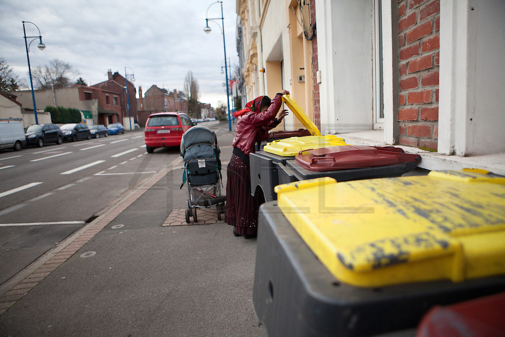 A Roma woman looking for useful things in the rubbish bins. //France is the land of destination of many Roma people in their diaspora across Europe, who live camped in many settlements at the outskirts of cities. In 2013, the French Government has expelled thousands of Gypsies from the East as in 2010, 2011 and 2012, this time without any financial aids. Many Roma live afraid to be expelled but they remain in the French country with the hope of receiving some kind of aid. Outskirts of Lille, France. December 2013.