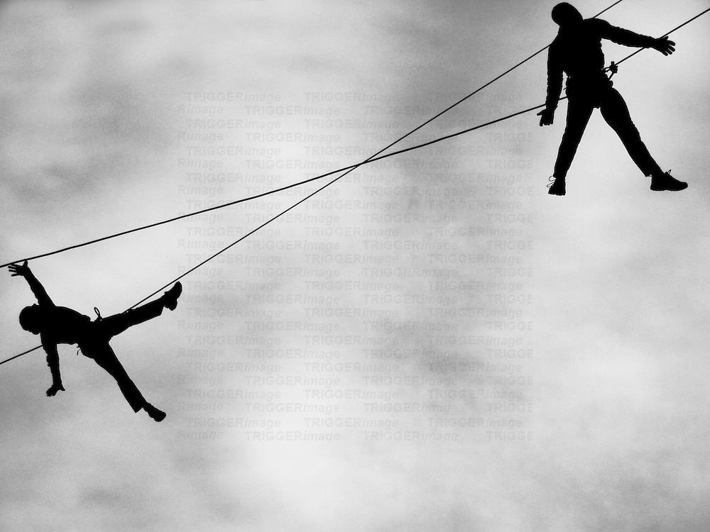 Two figures suspended from high wires
