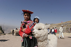 A young Peruivan girl with her cousin and alpaca atop the Incan ruins overlooking the city of Cusco, Peru<br />