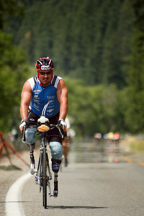 JEROME A. POLLOS/Press..Scott Rigsby powers his way along Coeur d'Alene Lake Drive toward Higgens Point during the 112-mile biking portion of Ironman. Rigsby set his sights on becoming the first double-leg amputee to complete an Ironman event.
