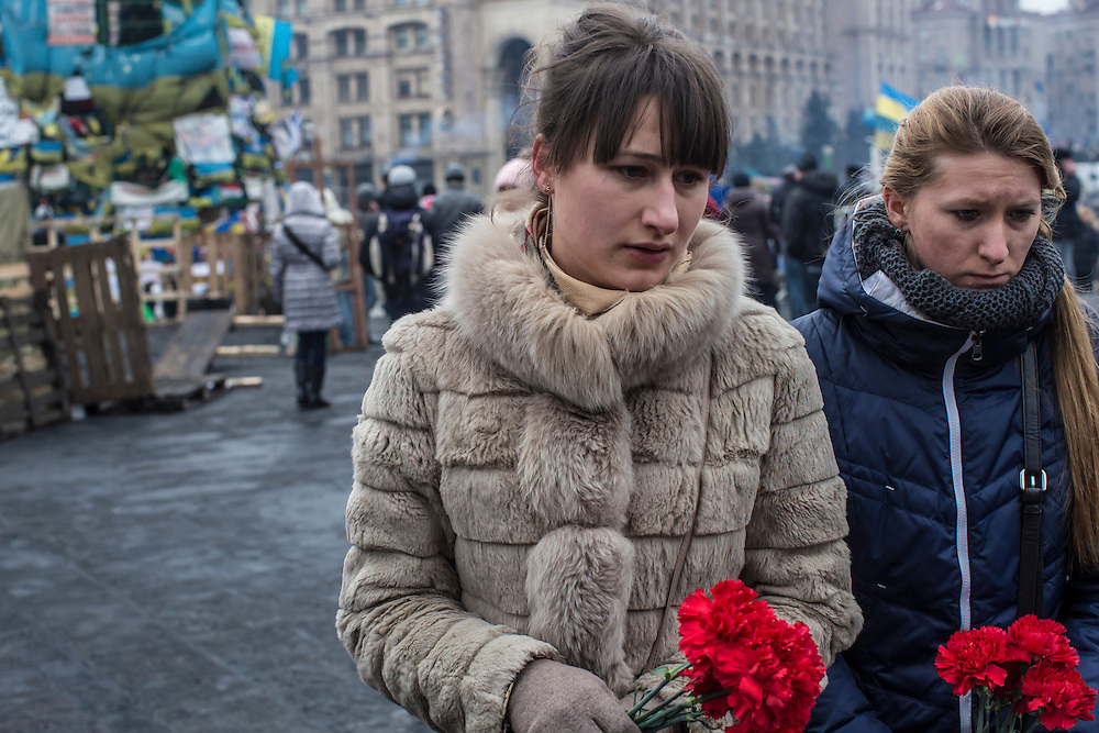 KIEV, UKRAINE - FEBRUARY 23: Women prepare to place flowers at a memorial to anti-government protesters killed in chashes with police on Independence Square on February 23, 2014 in Kiev, Ukraine. After a chaotic and violent week, Viktor Yanukovych has been ousted as President as the Ukrainian parliament moves forward with scheduling new elections and establishing a caretaker government. (Photo by Brendan Hoffman/Getty Images) *** Local Caption ***