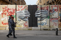 © Licensed to London News Pictures. 27/01/2020. Beirut, Lebanon. Lebanese police walk past graffiti artwork around the government buildings in Downtown Beirut, as the government votes on the 2020 budget. Anti government demonstrators have been campaigning against government corruption and economic crisis for 103 days in Lebanon. Photo credit : Tom Nicholson/LNP