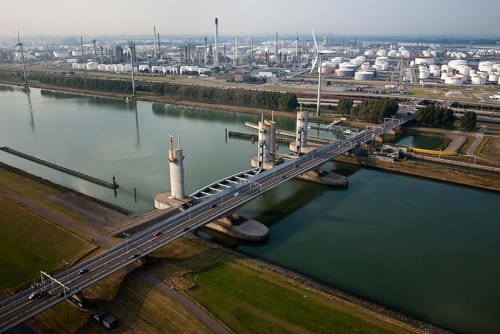 Nederland, Zuid-Holland, Botlek, 19-09-2009; Functioneringssluiting Hartelkering, de waterkering in het Hartelkanaal wordt een maal per jaar, voordat het stormseizoen begint, getest. Tijdens het sluiten van de kering ligt alle scheepvaartverkeer naar de Rotterdamse haven stil. .In de achtergrond Botlek en olieraffinaderij..De kering sluit normaal gesproken alleen bij dreigende stromvloed en bij een waterstand van 3 meter of meer boven NAP. De kering, onderdeel van de Deltawerken, vormt samen met de Maeslantkering  de Europoortkering en beschermt Rotterdam en achterland bij extreme waterstanden. .Netherlands, Rotterdam harbour. Aerial view of one of the two storm surge barriers. This barrier, the Hartelkering  in the Hartel canal, together with the greater nearby  Maeslant barrier (in the New Waterway), are tested during the so-called functioning closure, taking place one a year before the storm season begins. The waterway and canal, leading to the Port of Rotterdam, are closed during the test..luchtfoto (toeslag), aerial photo (additional fee required).foto/photo Siebe Swart