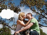 Young couple kissing with think bubble above woman's head