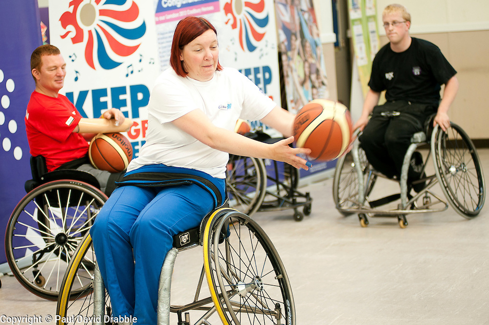 Cadbury 2012 Paralympic demonstration Sheffield..Kathryn Betts (London 2012 Site Ambassador for Sheffield) tries her hand at wheelchair basketball watched by coach Andy Atkinson and player Mike Porter who were on site with the  RGK Rhinos Sporting club wheelchair basketball team to give Sheffield colleagues an insight into Wheelchair basketball, Paralympic sports and promote awareness around the different sporting disciplines.   .  ....3 September 2012.Image © Paul David Drabble