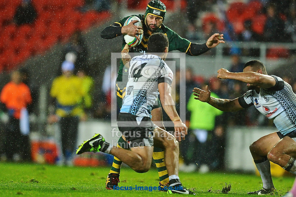 Picture by Ian Wadkins/Focus Images Ltd +44 7877 568959<br /> 02/11/2013<br /> Johnathan Thurston of Australia evades the challenge of Apisai Koroisau of Fiji during the Rugby League World Cup 2013 match at Langtree Park , St Helens.