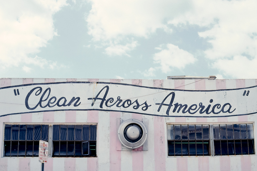 """Pink and white vertically striped building with """"Clean Across America"""" painted on it in Miami, Florida"""
