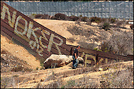 Un hombre camina al lado del muro fronterizo en Tijuana. (FOTO: Prometeo Lucero)
