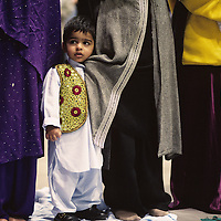 USA, Washington, Seattle, Makael Karim, 2, among line of women's robes at Eid-ul Adha prayers marking end of Islamic Hajj