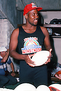 Miami Dolphins punter Reggie Roby autographs footballs in the locker room after practice the week of the 1990 NFL Pro Bowl between the National Football Conference and the American Football Conference on Jan. 30, 1990 in Honolulu. The NFC won the game 27-21. (©Paul Anthony Spinelli)