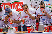 Competitive eater Joey Chestnut, who won $5,000 first prize in the Famous Famiglia world championship pizza eating contest in New York City's Times Square by eating 45 slices of cheese pizza in 10 minutes. (Joey Chestnut is featured in the book What I Eat: Around the World in 80 Diets.)  Each slice weighed 109 grams (3.84 ounces) (3.84 ounces) and contained 260 calories. In ten minutes Joey consumed 10.81 pounds (4.9 kilograms) of pizza and drank a gallon of water. The pizza contained 11,700 calories. Joey is on the stage between the man in the blue cap and the man with the mohawk hairstyle.