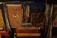 Mongolia  Tanka and Sutra in a buddhist temple in a yurt  / Tanka et sutra dans un temple-yourte. (Sum de IK UUL dans l'aymag de ZAVQAN,Mongolie)  En attendant la finition de la construction du nouveau temple, on officie dans une large yourte transformée en lieu de culte. Là, les trésors longtemps dispersés et conservés par les laïcs pendant toutes les années du communisme, s'amassent peu à peu et retrouvent leur destination première. VAJRAPANI à gauche et YAMANTAKA à droite sont deux divinités terribles protectrices de la religion. Devant, les textes religieux (sudar) enroulés soigneusement dans un tissu soyeux ou rangés dans une boîte spéciale, sont empilés par ordre de taille.
