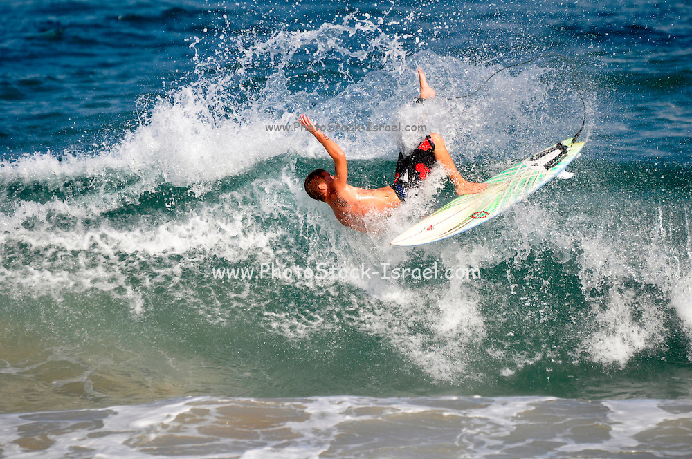 Israel, Mediterranean sea, Surfer falls of his board during a spin on the crest of a wave