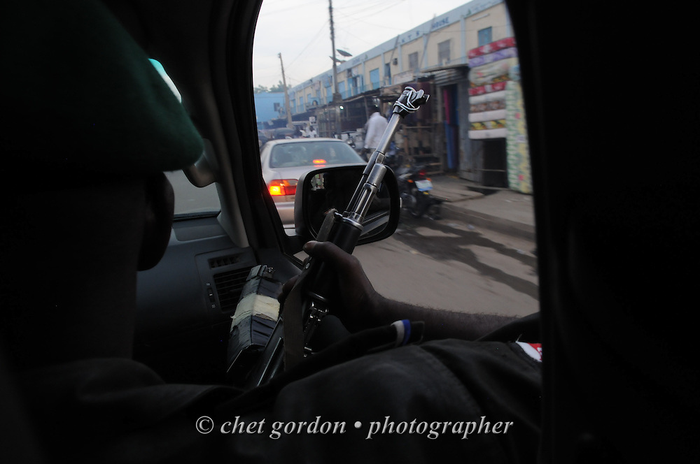 A Nigerian policeman rides in the backseat of an escort vehicle in Kano, Nigeria on Monday, December 3, 2012. A police officer directing traffic was killed the same day when a roadside bomb exploded near his intersection in Kano.