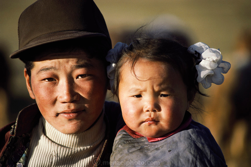 Rural life 35km from Ulaanbaatar, Mongolia. An older brother holds his young sister. The live in a traditional ger (round tent built from canvas, strong poles, and wool felt).  Material World Project.