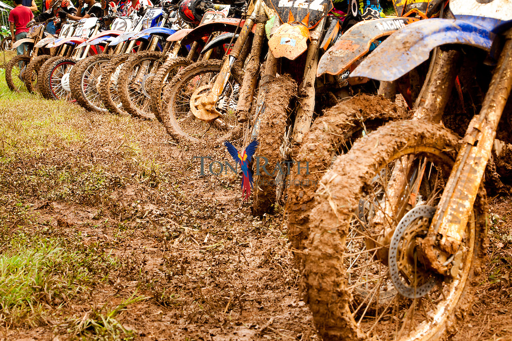 Telephoto shot of motorcycle wheels plastered with mud as they stand at the starting line of an outdoor motocross track in Belmopan Belize.