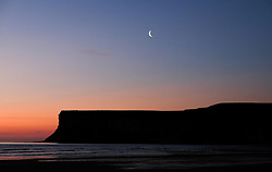© Licensed to London News Pictures.12/06/15<br /> Saltburn by the Sea, England<br /> <br /> A crescent moon can be seen above Huntcliff as dawn breaks over Saltburn by the Sea.<br /> <br /> Photo credit : Ian Forsyth/LNP