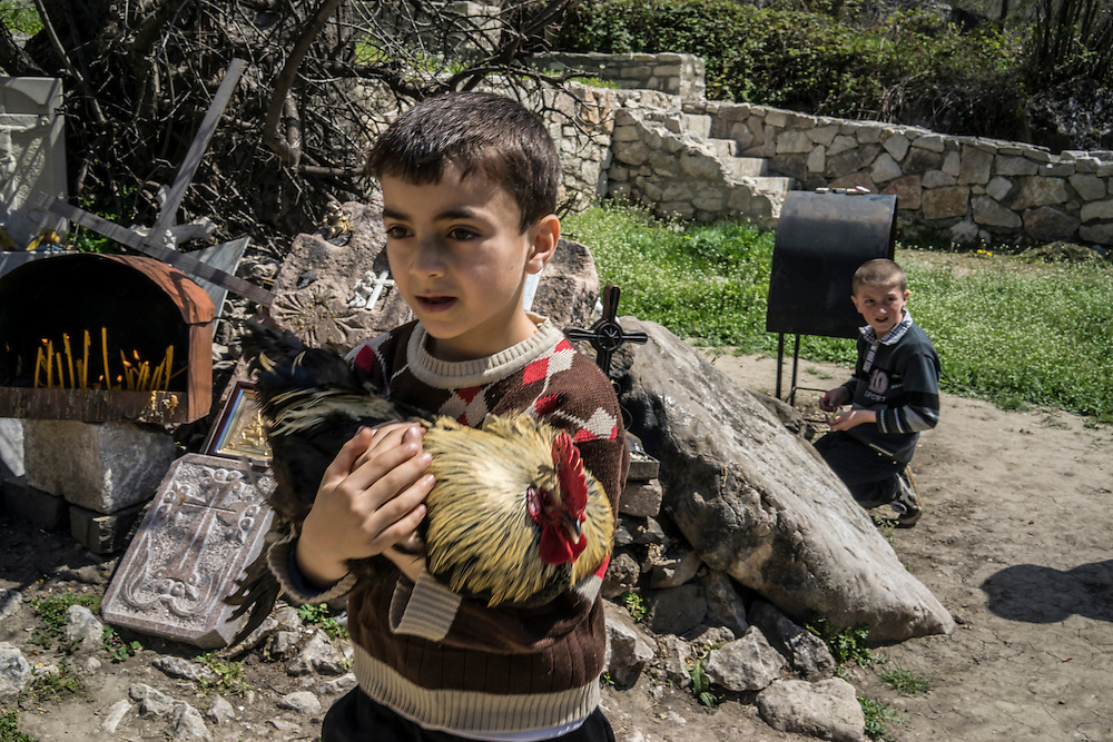 KARASHEN, NAGORNO-KARABAKH - APRIL 19: Aram Aslanyan, 6, carries a chicken which his family will kill in sacrifice in order to bring good fortune on April 19, 2015 in Karashen, Nagorno-Karabakh. Since signing a ceasefire in a war with Azerbaijan in 1994, Nagorno-Karabakh, officially part of Azerbaijan, has functioned as a self-declared independent republic and de facto part of Armenia, with hostilities along the line of contact between Nagorno-Karabakh and Azerbaijan occasionally flaring up and causing casualties. (Photo by Brendan Hoffman/Getty Images) *** Local Caption *** Aram Aslanyan