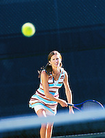 A young woman serving in a tennis match<br />