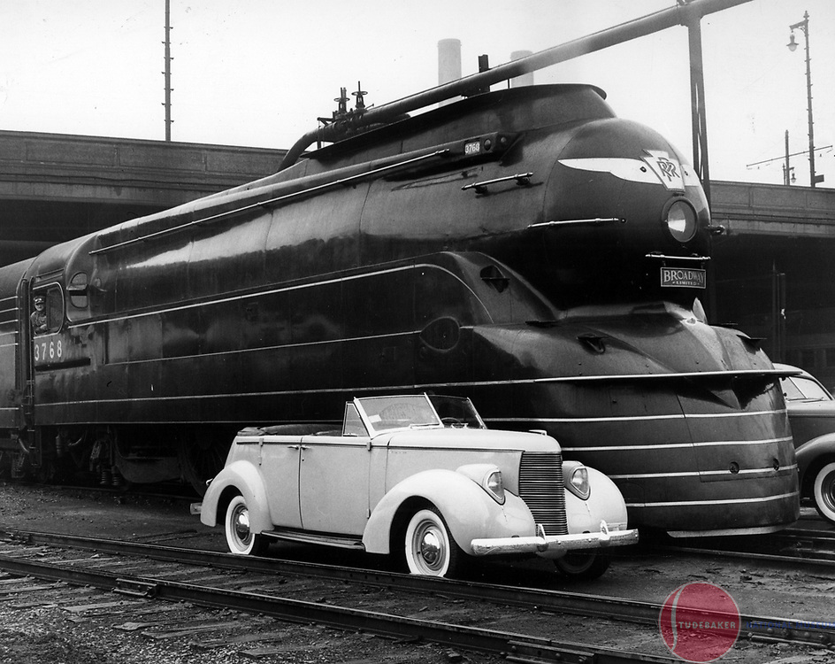 A 1938 Studebaker Commander Convertible Sedan next to the Pennsylvania Railroad's Broadway Limited.