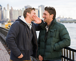 two men talking and laughing on a walkway by the Hudson River in New Jersey