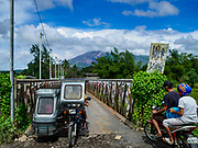 21 JANUARY 2018 - DARAGA, ALBAY, PHILIPPINES:  A tricycle taxi crosses a small bridge over the Yawa River while the Mayon volcano, in the background, belches smoke and ash. Mayon volcano, the most active volcano in the Philippines.  More than 30,000 people have been evacuated from communities on the near the Mayon volcano in Albay province in the Philippines. Most of the evacuees are staying at schools in communities outside of the evacuation zone.   PHOTO BY JACK KURTZ