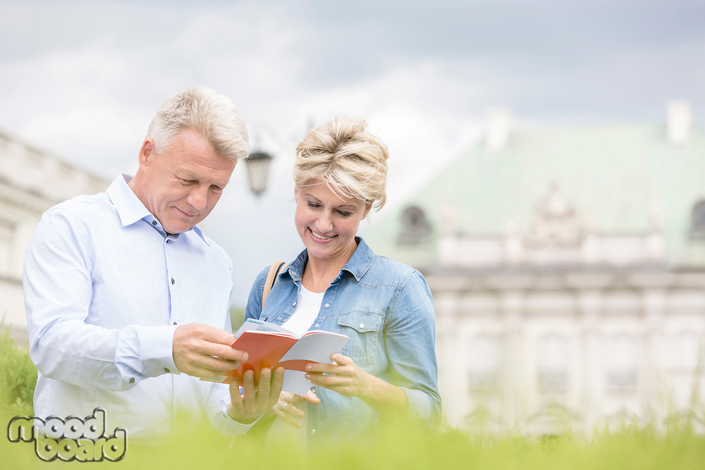 Smiling middle-aged couple reading guidebook outdoors