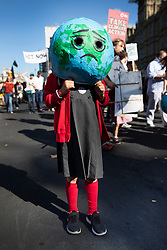 © Licensed to London News Pictures. 20/09/2019. London, UK. A young activist wears a 'sad face' planet on her head as she takes part in the Global Climate Strike demonstration near Parliament. Thousands of similar actions are taking place all over the UK and the rest of the world. Photo credit: Peter Macdiarmid/LNP