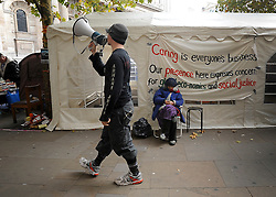 © Licensed to London News Pictures. 02/11/2011. London, UK. A man with a loud hailer walks past a sleeping woman at the camp. Occupy London protesters outside St Paul's Cathedral today, 2nd November 2011.  Photo credit : Stephen Simpson/LNP