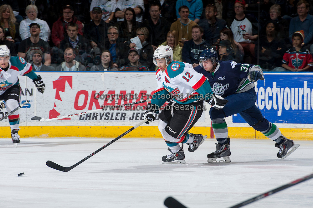 KELOWNA, CANADA - APRIL 3: Jared Hauf #33 of the Seattle Thunderbirds stick checks Tyrell Goulbourne #12 of the Kelowna Rockets as he skates for the puck on April 3, 2014 during Game 1 of the second round of WHL Playoffs at Prospera Place in Kelowna, British Columbia, Canada.   (Photo by Marissa Baecker/Getty Images)  *** Local Caption *** Jared Hauf; Tyrell Goulbourne;