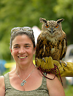 Old Westbury, New York, U.S. - August 23, 2014 - CATHY HORVATH is with AUGIE, a 4-year-old male Eurasian Eagle Owl (Bubo bubo) with large orange eyes, from WINORR, Wildlife in Need of Rescue and Rehabilitation, at the 54th Annual Long Island Scottish Festival and Highland Games, co-hosted by L. I. Scottish Clan MacDuff, at Old Westbury Gardens. WINORR is run by CAthy and her husband Bobby, licensed animal rehabilitators in North Massapequa.