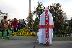 © licensed to London News Pictures. London, UK 21/04/2012. A woman with a English flag on her back enjoying the St George's Day celebrations in Trafalgar Square as the London landmark transformed into an English garden ahead of St George's Day. Photo credit: Tolga Akmen/LNP