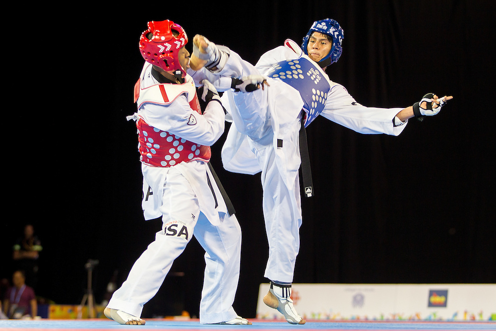 Miguel Angel Trejos of Colombia kicks Terrence Jennings of the United States during their bronze medal contest in the men's Taekwondo -68kg division of at the 2015 Pan American Games in Toronto, Canada, July 20,  2015.  AFP PHOTO/GEOFF ROBINS