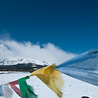 Tibetan Prayer Flags blowing in the wind with mountain backdrop Glacier National Park, Montana