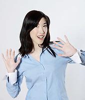 studio shot portrait of a beautiful southeast asian young woman waving