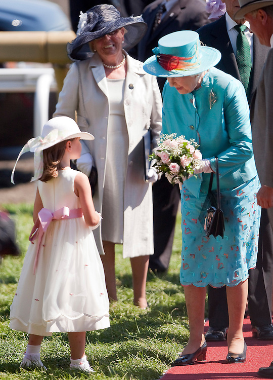 Queen Elizabeth II accepts flowers from a young girl as she arrives at Woodbine racetrack in Toronto, Canada for the 151st running of the Queen's Plate, July 4, 2010. <br /> AFP/GEOFF ROBINS/STR