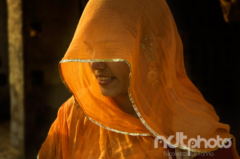 Light filtering through her veil shows the hidden eyes and jewels of a young woman in Rajasthan, India