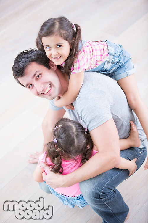 High angle portrait of playful father carrying girls at home