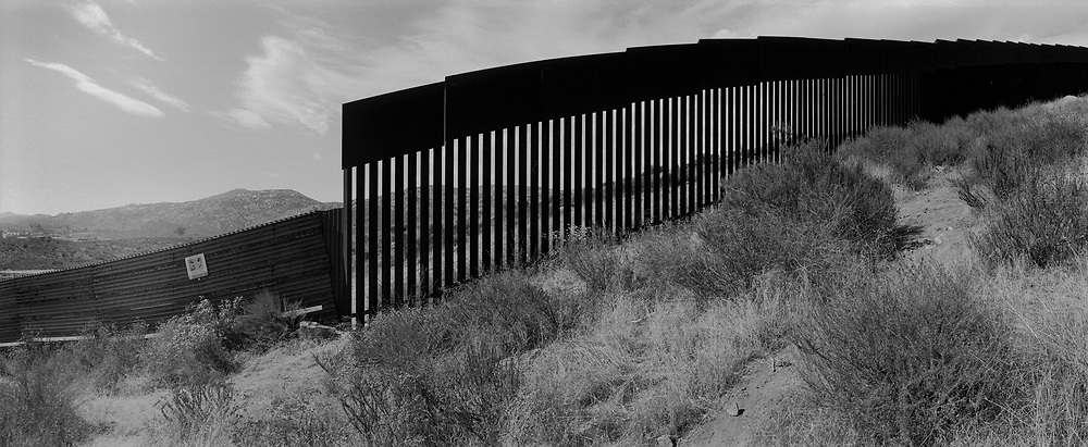 A section of the old U.S. border fence meeting up with a newer taller section of the fence seen west of Tecate Mexico looking north towards the United States..(Credit Image: © Louie Palu/ZUMA Press)